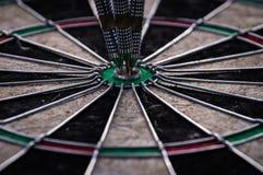 Τρία βέλη βελών που χτυπούν στο κέντρο στόχων του dartboard Στοκ Εικόνες