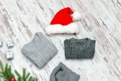 Τρία γκρίζα πουλόβερ και καπέλο Santa ` s σε ένα ξύλινο υπόβαθρο Fash Στοκ Φωτογραφία