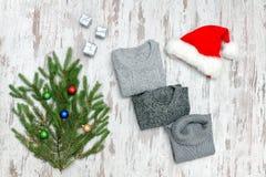 Τρία γκρίζα πουλόβερ, το καπέλο Santa ` s και το έλατο διακλαδίζονται σε μια ξύλινη πλάτη Στοκ Εικόνες
