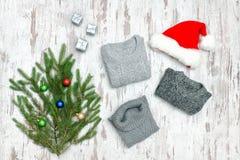 Τρία γκρίζα πουλόβερ, το καπέλο Santa ` s και το έλατο διακλαδίζονται σε μια ξύλινη πλάτη Στοκ Φωτογραφία