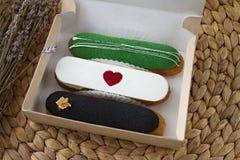 Τρία γλυκά εύγευστα πολύχρωμα eclairs με μια κόκκινη καρδιά σε ένα κουτί από χαρτόνι ως δώρο και ανθοδέσμη Στοκ Εικόνες