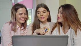 Τρία γοητευτικά κορίτσια κολλεγίων που γελούν και που μιλούν μελετώντας από κοινού φιλμ μικρού μήκους