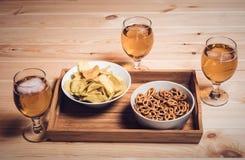 Τρία γυαλιά μπύρας και πρόχειρα φαγητά μπύρας στον ξύλινο πίνακα Εκλεκτής ποιότητας styl Στοκ φωτογραφία με δικαίωμα ελεύθερης χρήσης