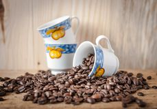 Τρία διακοσμητικά φλυτζάνια καφέ και διεσπαρμένα σιτάρια του πρόσφατα ψημένου καφέ Στοκ φωτογραφία με δικαίωμα ελεύθερης χρήσης