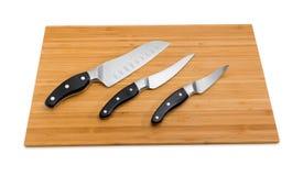 Τρία διαφορετικά μαχαίρια κουζινών στον τέμνοντα πίνακα μπαμπού Στοκ Φωτογραφία