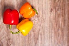 Τρία εγχώρια πιπέρια στο ξύλινο επιτραπέζιο υπόβαθρο Γλυκιά πάπρικα στην κουζίνα Στοκ εικόνα με δικαίωμα ελεύθερης χρήσης