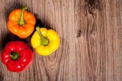 Τρία εγχώρια πιπέρια στο ξύλινο επιτραπέζιο υπόβαθρο Γλυκιά πάπρικα στην κουζίνα Στοκ φωτογραφία με δικαίωμα ελεύθερης χρήσης