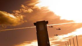 Τρία ελικόπτερα apache που πετούν μετά από έναν πύργο με τα σύννεφα Στοκ φωτογραφία με δικαίωμα ελεύθερης χρήσης