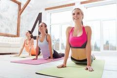 Τρία ενεργά κορίτσια που κάνουν το τέντωμα μετά από την ομάδα workout Στοκ εικόνες με δικαίωμα ελεύθερης χρήσης