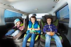 Τρία ευτυχή αγόρια που κάθονται στα καθίσματα αυτοκινήτων ασφάλειας Στοκ φωτογραφία με δικαίωμα ελεύθερης χρήσης