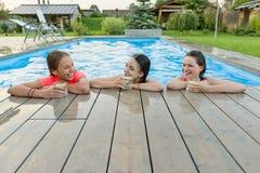 Τρία ευτυχή κορίτσια με τα ποτά στο θερινό κόμμα στην πισίνα στοκ εικόνα με δικαίωμα ελεύθερης χρήσης