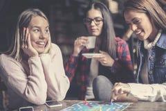 Τρία ευτυχή κορίτσια που παίζουν το επιτραπέζιο παιχνίδι στοκ εικόνες
