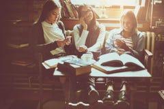 Τρία ευτυχή κορίτσια σπουδαστών που διδάσκουν στον καφέ στοκ εικόνες