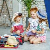 Τρία ευτυχή παιδιά συσκευάζουν τα ενδύματά τους σε μια βαλίτσα Έννοια, στοκ φωτογραφίες