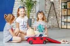 Τρία ευτυχή παιδιά των κοριτσιών συσκευάζουν μια βαλίτσα σε ένα ταξίδι Έννοια στοκ εικόνες με δικαίωμα ελεύθερης χρήσης