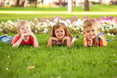 Τρία ευτυχή παιδιά που βρίσκονται στο χορτοτάπητα. Στοκ φωτογραφίες με δικαίωμα ελεύθερης χρήσης