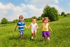 Τρία ευτυχή παιδιά που κρατούν τα χέρια και το παιχνίδι Στοκ Φωτογραφία