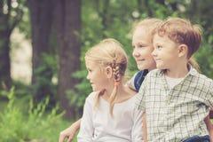 Τρία ευτυχή παιδιά που παίζουν στο πάρκο στο χρόνο ημέρας Στοκ εικόνα με δικαίωμα ελεύθερης χρήσης