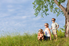 Τρία ευτυχή παιδιά που παίζουν στο πάρκο στο χρόνο ημέρας Στοκ εικόνες με δικαίωμα ελεύθερης χρήσης