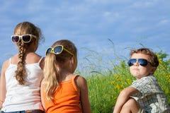 Τρία ευτυχή παιδιά που παίζουν στο πάρκο στο χρόνο ημέρας Στοκ φωτογραφία με δικαίωμα ελεύθερης χρήσης