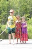 Τρία ευτυχή παιδιά στο πράσινο δασικό υπόβαθρο Στοκ φωτογραφίες με δικαίωμα ελεύθερης χρήσης