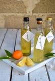 Τρία εύγευστα κίτρινα ποτά οινοπνεύματος στα μπουκάλια γυαλιού και το εσπεριδοειδές Πορτοκαλής-αρωματικό ηδύποτο, ιταλικό ποτό Li Στοκ Εικόνες