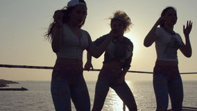 Τρία εύθυμα κορίτσια έντυσαν στις ίδιες περικνημίδες που χορεύουν στο ηλιοβασίλεμα κοντά στη θάλασσα απόθεμα βίντεο