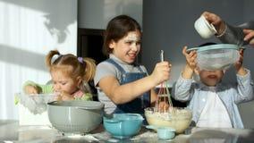Τρία εύθυμα παιδιά στην κουζίνα ζυμώνουν τη ζύμη για τις πίτες Το Mom τους βοηθά να κοσκινίσουν το αλεύρι Οικογενειακό μαγείρεμα  απόθεμα βίντεο