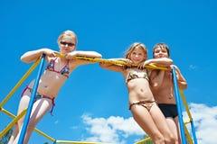 Τρία εύθυμα παιδιά στο φραγμό στην παιδική χαρά στοκ φωτογραφίες