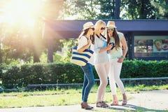Τρία ελκυστικά κορίτσια που εξετάζουν τις φωτογραφίες στη κάμερα τους στις καλοκαιρινές διακοπές στοκ φωτογραφία με δικαίωμα ελεύθερης χρήσης
