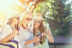 Τρία ελκυστικά κορίτσια που εξετάζουν τις φωτογραφίες στη κάμερα τους στις καλοκαιρινές διακοπές στοκ εικόνες