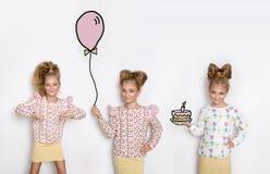 Τρία ζαλίζοντας όμορφα μικρά κορίτσια με τα μακριά ξανθά μαλλιά που στέκονται σε ένα άσπρο υπόβαθρο και ένας από τους κρατούν ένα στοκ εικόνες