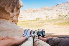Τρία ζευγάρια των ποδιών στα πάνινα παπούτσια σε ένα υπόβαθρο των βουνών στοκ φωτογραφία