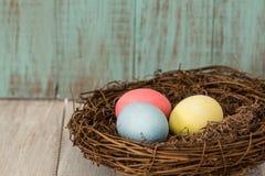 Τρία ζωηρόχρωμα αυγά Πάσχας σε μια φωλιά Στοκ φωτογραφία με δικαίωμα ελεύθερης χρήσης