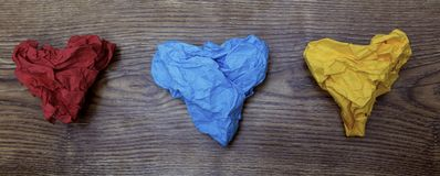 Τρία ζωηρόχρωμα διαμορφωμένα καρδιά τσαλακωμένα έγγραφα για τον ξύλινο πίνακα Βαλεντίνος ` s Ημέρα εραστών ` s Έννοια στις 14 Φεβ Στοκ φωτογραφία με δικαίωμα ελεύθερης χρήσης