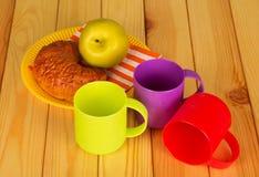 Τρία ζωηρόχρωμα πλαστικά φλυτζάνια, ένας croissant και η Apple στο πιάτο, στο υπόβαθρο του πίνακα Στοκ Εικόνες
