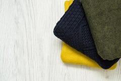 Τρία θερμά πουλόβερ χρώματος σε ένα ξύλινο υπόβαθρο Μοντέρνο γ Στοκ Εικόνες