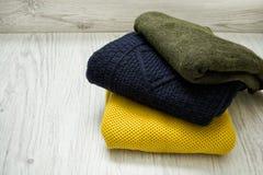 Τρία θερμά πουλόβερ χρώματος σε ένα ξύλινο υπόβαθρο Μοντέρνο γ Στοκ φωτογραφία με δικαίωμα ελεύθερης χρήσης