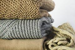 Τρία θερμά πουλόβερ και ένα μαντίλι σε έναν σωρό άσπρο σε έναν ξύλινο αυτή Στοκ Φωτογραφίες
