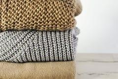 Τρία θερμά πουλόβερ σε έναν σωρό σε ένα άσπρο ξύλινο ράφι σε ένα ligh Στοκ Φωτογραφίες