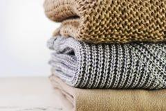Τρία θερμά πουλόβερ συσσωρεύονται στον πίνακα σε ένα ελαφρύ backgrou Στοκ Εικόνα