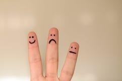 Τρία διαφορετικά emoticons δίνουν επισυμένος την προσοχή στα δάχτυλα Στοκ φωτογραφία με δικαίωμα ελεύθερης χρήσης