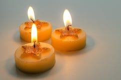 Τρία καίγοντας διακοσμητικά κεριά με το σχέδιο αστεριών Στοκ Εικόνες