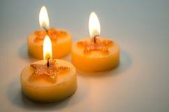Τρία καίγοντας διακοσμητικά κεριά με το σχέδιο αστεριών Στοκ Εικόνα