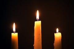 Τρία καίγοντας κεριά κεριών σε ένα μαύρο υπόβαθρο, θρησκεία, holid Στοκ Εικόνα