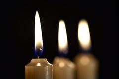 Τρία καίγοντας κεριά κεριών σε ένα μαύρο υπόβαθρο Στοκ Εικόνες