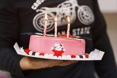 Τρία καίγοντας κεριά στο ρόδινο bithday κέικ Στοκ Φωτογραφία