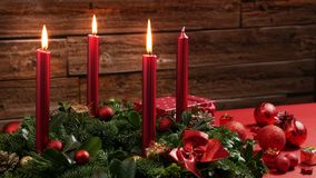 Τρία καίγοντας κόκκινα κεριά σε ένα παραδοσιακό στεφάνι εμφάνισης με την εορταστική διακόσμηση φιλμ μικρού μήκους