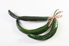 Τρία καμμμένα πράσινα πιπέρια chilaca που δένονται με τον κόκκινο σπάγγο κάνναβης που απομονώνεται στο λευκό στοκ φωτογραφίες