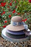 Τρία καπέλα αχύρου που συσσωρεύονται στον πίνακα στον κήπο Στοκ φωτογραφία με δικαίωμα ελεύθερης χρήσης